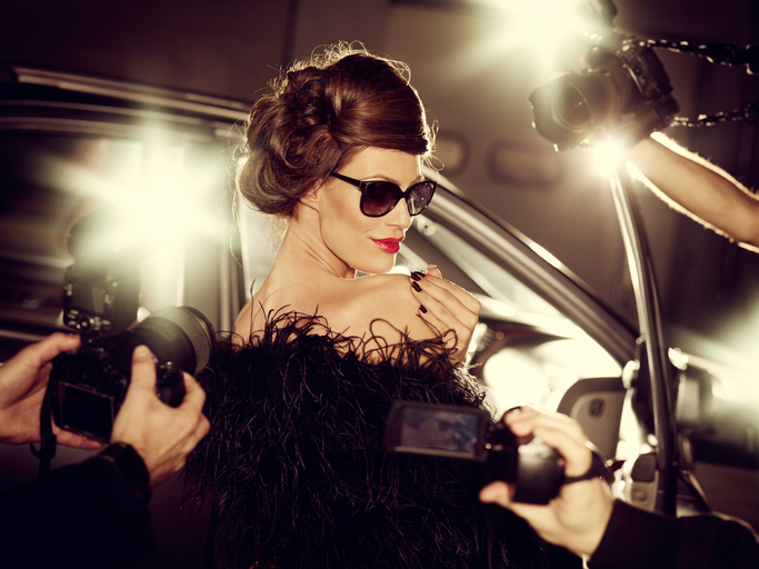 Glamorous celebrity woman surrounded by paparazzi photographers on a red carpet in front of her car.