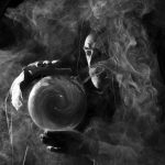 Fortune teller in fantastical costume holding crystal ball, smoky atmosphere