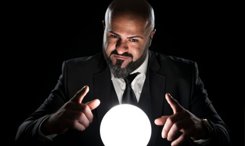 A fortune teller sitting at a desk gesturing at a glowing crystal ball. The bald man with the long beard wearing an elegant black suit, a white button down shirt and a tie. He is looking at the camera.