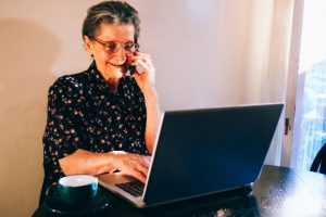 Grandmother sitting at the kitchen table, talking on a cell phone, and using laptop. Elderly woman drinking coffee near the window and typing on a laptop keyboard, while holding a smartphone and talking.