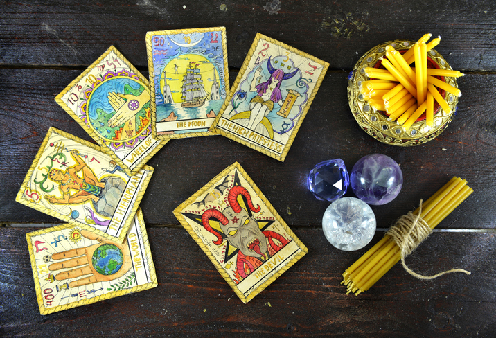 Background with candles, crystal and deck of the tarot cards on old table. Fortune telling seance or black magic ritual. Scary still life with occult and esoteric symbols. Halloween or divination rite